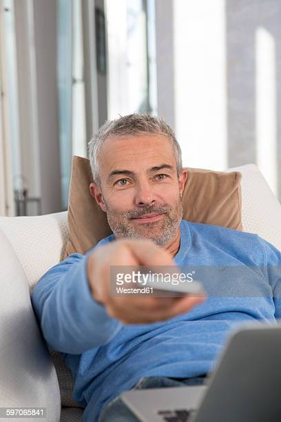 Mature man sitting on couch with laptop, using remote control