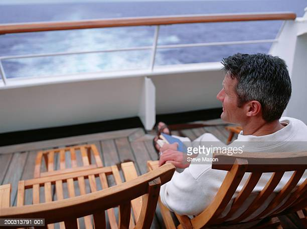 Mature man sitting on deckchair on cruise ship