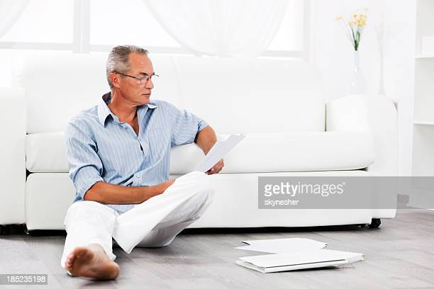 Mature man sitting on floor and looking at documents.
