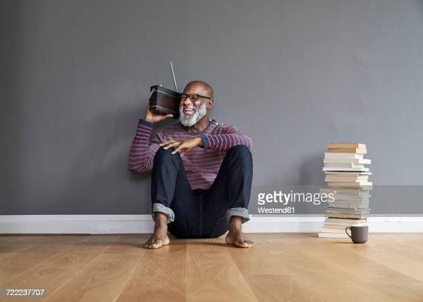 Mature man sitting on floor listening to the radio, laughing