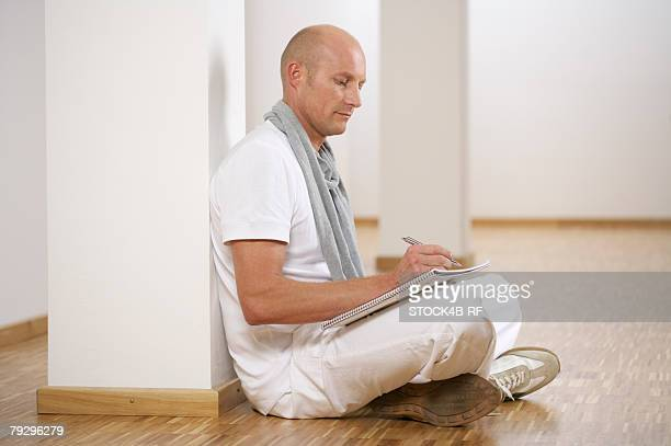 mature man sitting on floor while making notes - completamente calvo foto e immagini stock