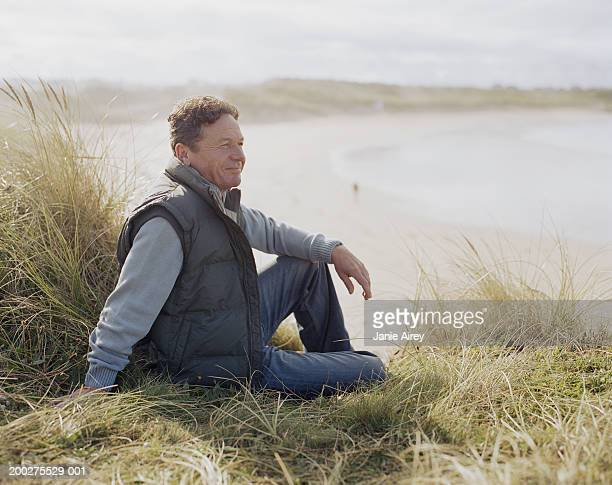 Mature man sitting on grass by beach, smiling