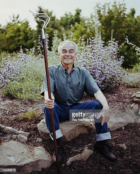 mature man sitting on rock, holding rake - botanischer garten stock-fotos und bilder