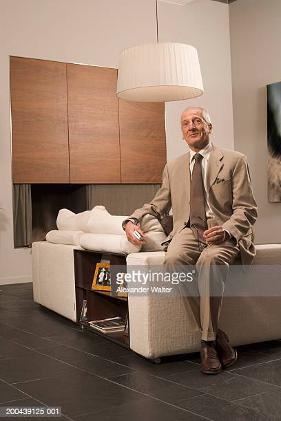 mature man sitting on side of sofa, wearing suit, smiling, portrait - beige suit stock pictures, royalty-free photos & images