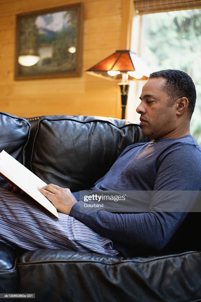 Mature man sitting on sofa and reading, side view : Foto stock