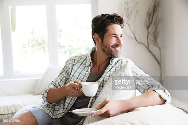 Mature man sitting on sofa, drinking coffee