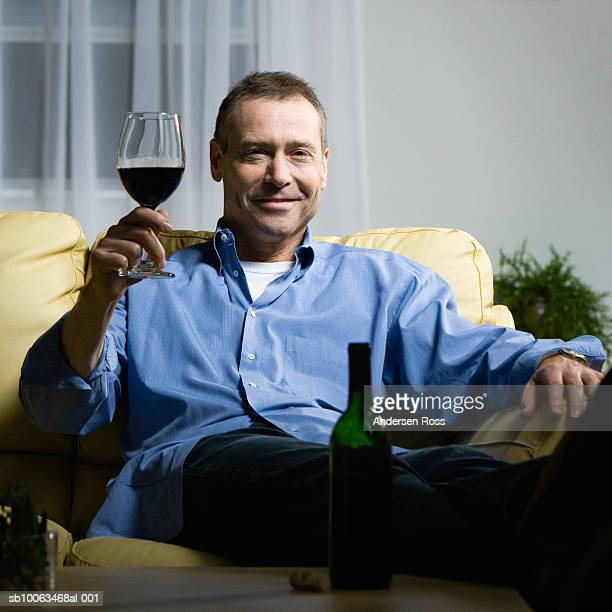 Mature man sitting on sofa holding wine, portrait