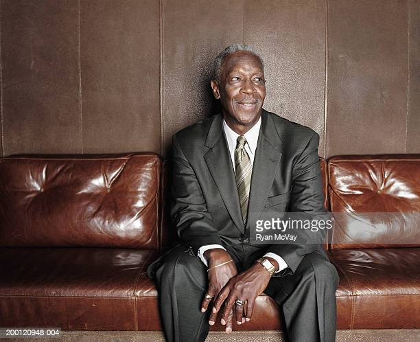 mature man sitting on sofa, smiling - brown suit stock photos and pictures
