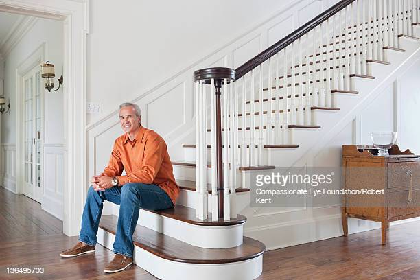 Mature man sitting on stairs in entrance hall