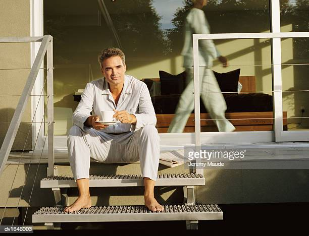 mature man sitting on steps holding a cup and saucer - woman sitting on man's lap stock pictures, royalty-free photos & images