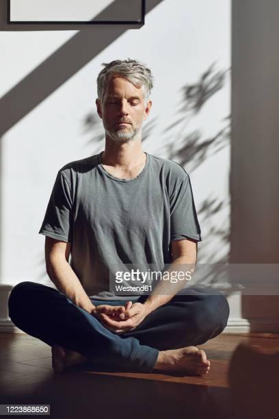 mature man sitting on the floor at home meditating - alles hinter sich lassen stock-fotos und bilder