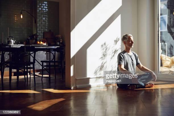 mature man sitting on the floor at home meditating - entspannungsübung stock-fotos und bilder