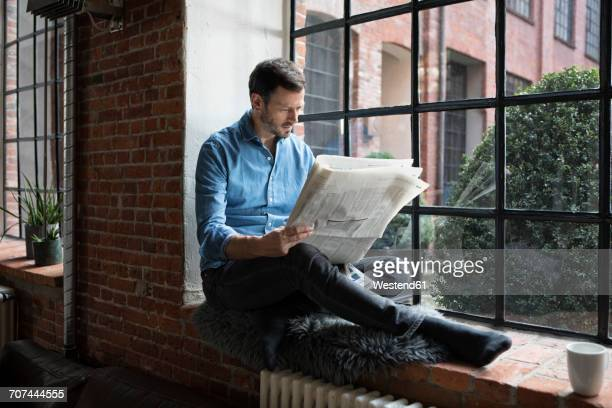 Mature man sitting on window sill, reading newspaper