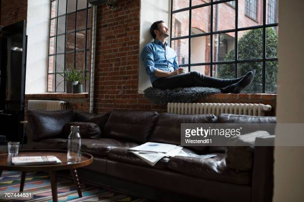 mature man sitting on window sill, relaxing with cup of coffee - loft stock photos and pictures