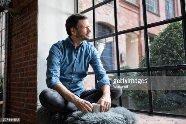 Mature man sitting on window sill, relaxing with cup of coffee