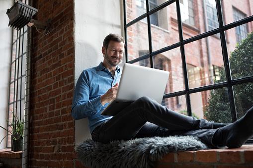 Mature man sitting on window sill, using laptop - gettyimageskorea