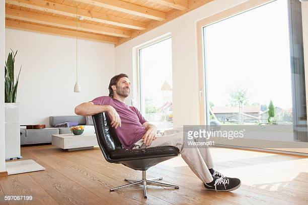 Mature man sitting relaxed in his living room