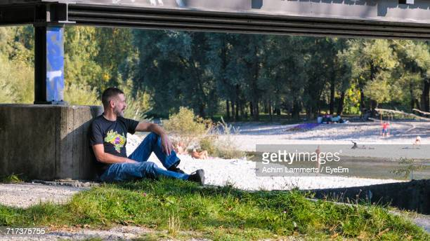 mature man sitting under bridge - achim lammerts fotografías e imágenes de stock