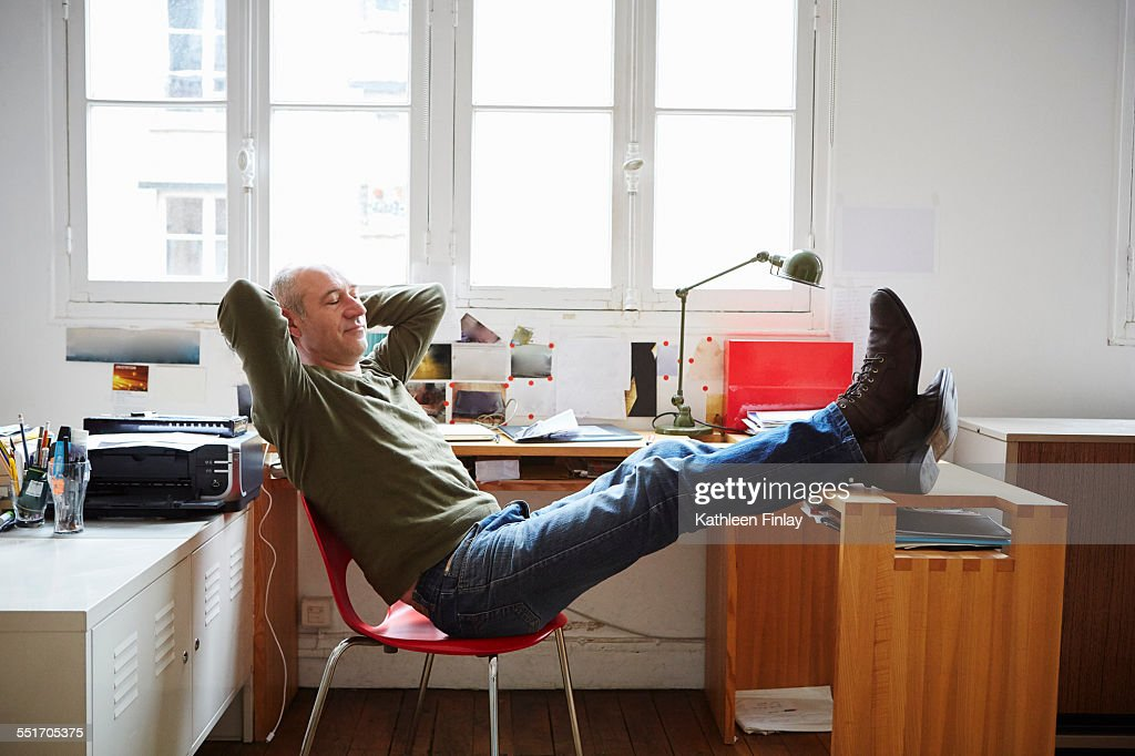 Man Sitting With Feet Up At Desk Stock Photo
