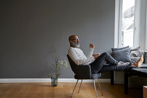 Mature man sitting with feet up, using smartphone - gettyimageskorea
