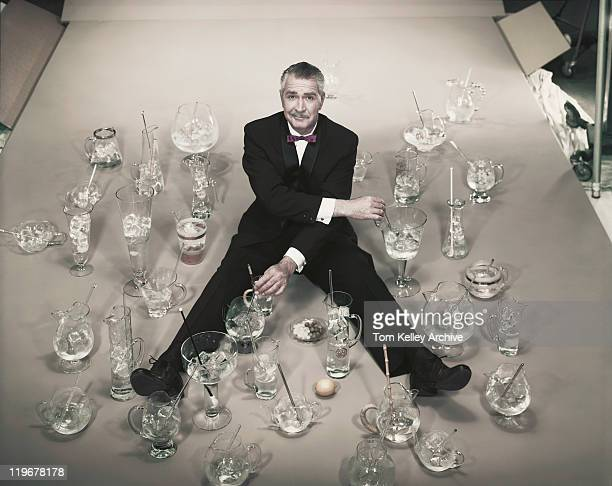 mature man sitting with stirring glasses of ice - 1957 stockfoto's en -beelden