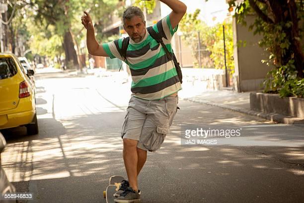 Mature man skateboarding on street, Rio De Janeiro, Brazil