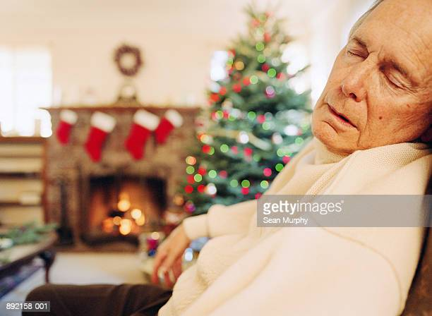 Mature man sleeping in chair, christmas tree in background