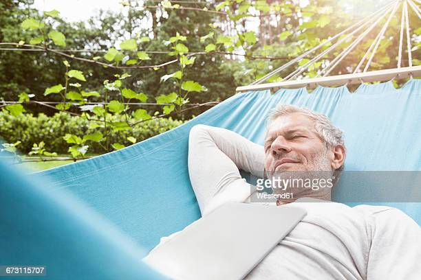 mature man sleeping in hammock with digital tablet on his chest - hamac photos et images de collection
