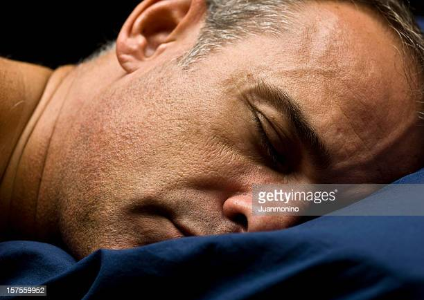 Mature man sleeping on a blue pillow