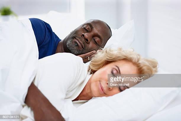 Reifer Mann Schlafen auf dem Bett mit der Frau