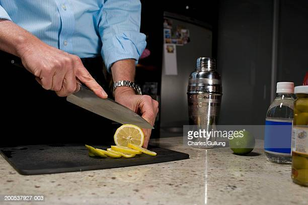 Mature man slicing lemon beside cocktail shaker, mid section