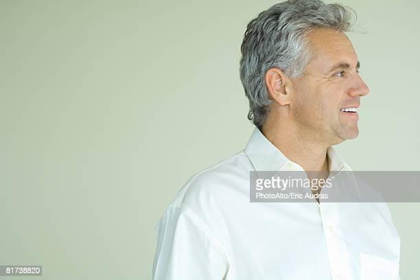 mature man smiling, looking away, head and shoulders, portrait - homme profil photos et images de collection