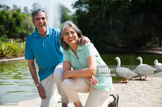Mature man smiling with his arm around his wife, Lodi Gardens, New Delhi, India