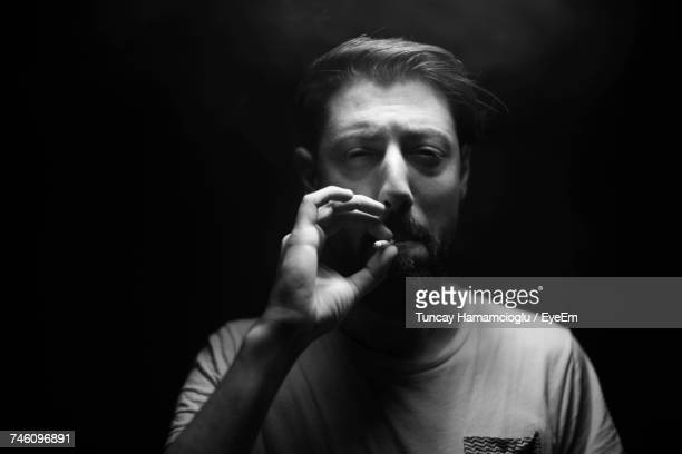 Mature Man Smoking Cigarette Against Black Background