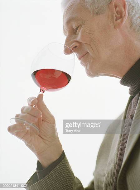 Mature man sniffing glass of red wine