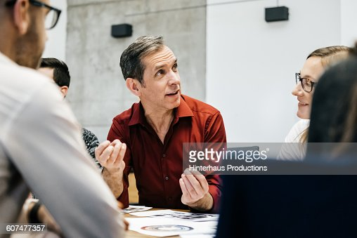 MAture man speaking in a business meeting.