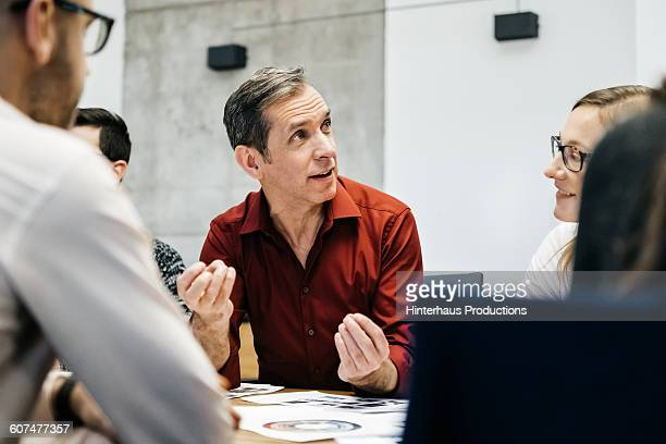 mature man speaking in a business meeting. - zakenbijeenkomst stockfoto's en -beelden