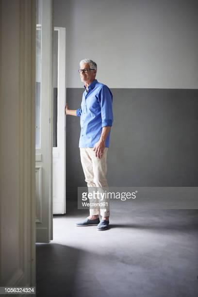 Mature man standing at open balcony door