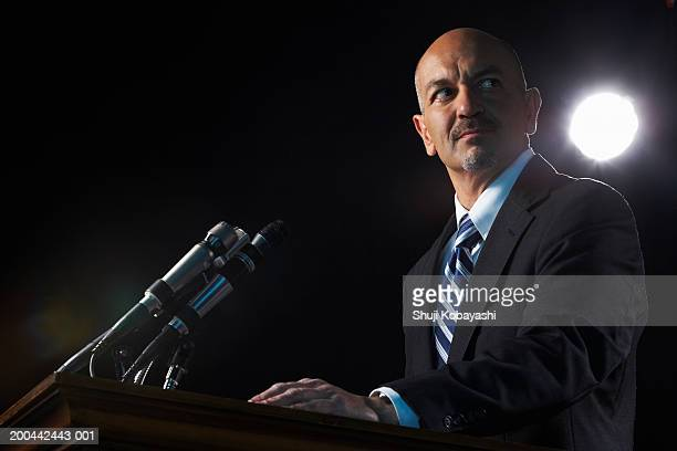 mature man standing at podium, low angle view - politician stock pictures, royalty-free photos & images