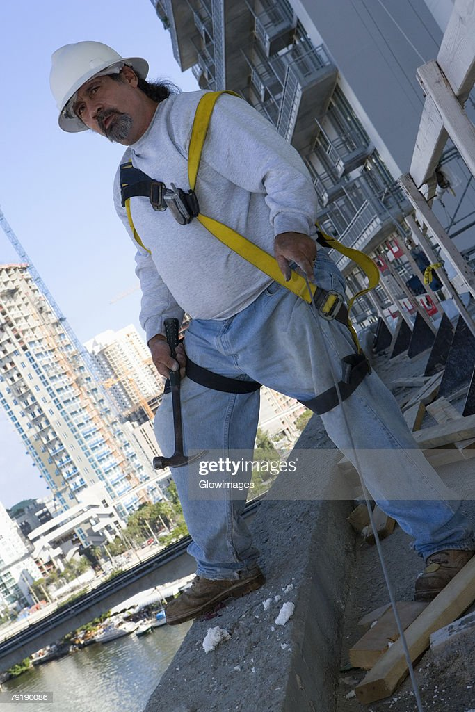 Mature man standing at the edge of a building and holding a hammer : Foto de stock