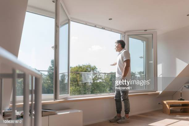 Mature man standing at the window in empty room