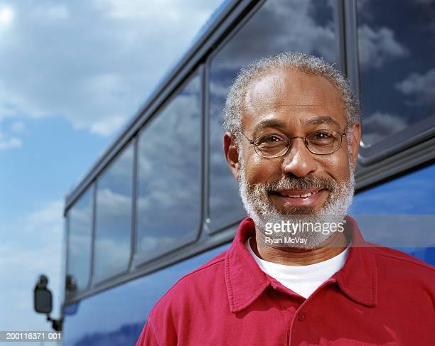 Mature man standing beside coach bus, smiling, portrait