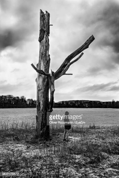 Mature Man Standing By Dead Tree At Lakeshore