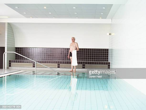 Mature man standing by indoor swimming pool, holding towel