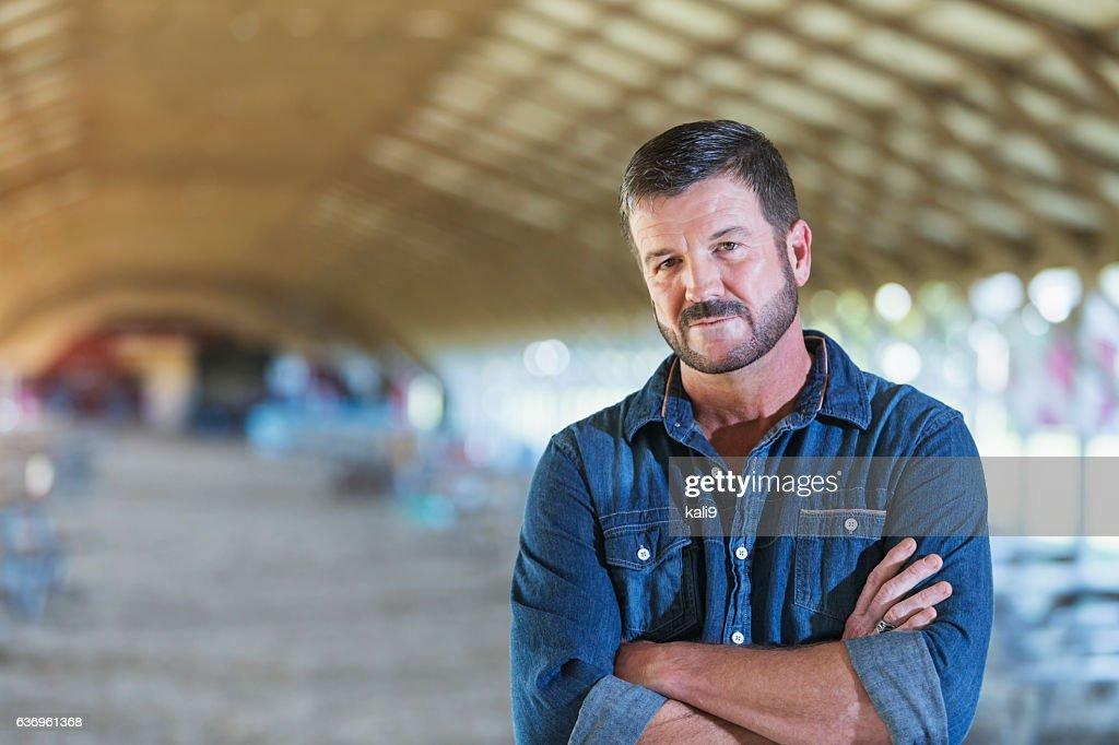 Mature man standing in barn : Stock-Foto