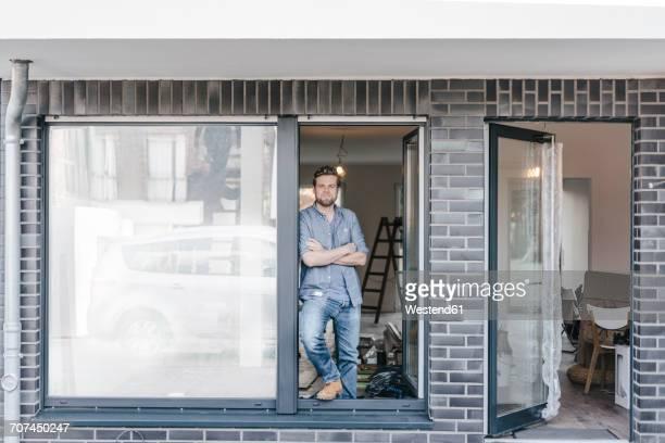 Mature man standing in door of his new home