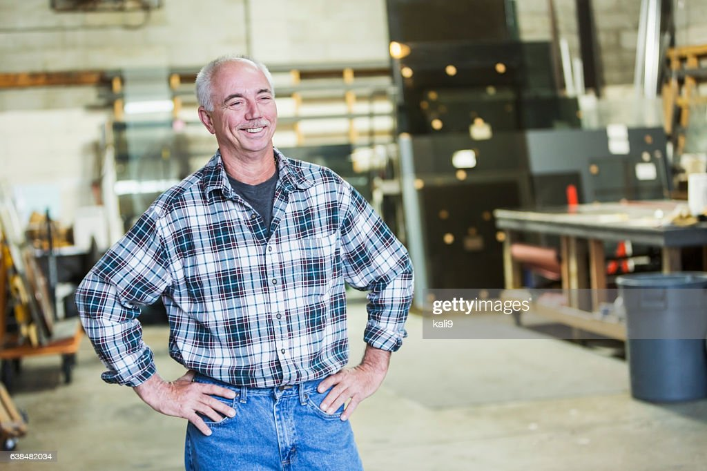 Mature man standing in factory workshop : Stock-Foto