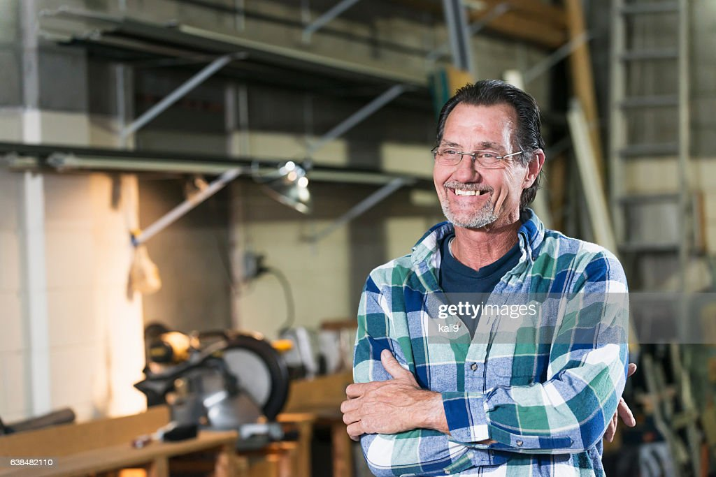 Mature man standing in factory workshop : Stock-Foto