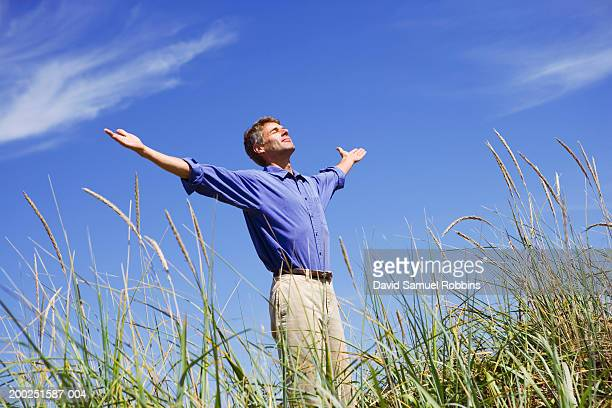 Mature man standing in field, arms outstretched, eyes closed