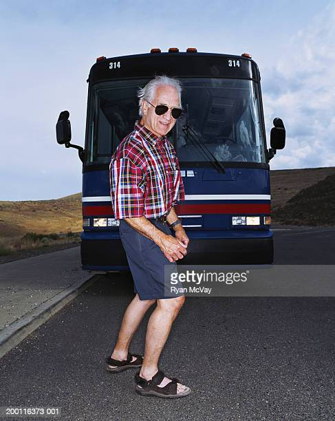 Mature man standing in front of coach bus, smiling, portrait
